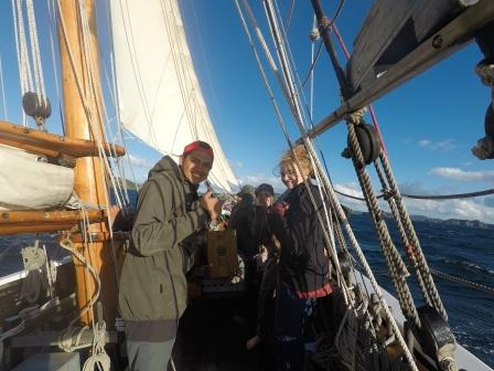 Trainees hoisting sail with thumbs up